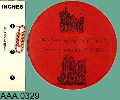 "This artifact is a red button with black text, and a church drawing.  The text reads:  ""The First Congregational Church - Corona, CA - 1887-1987."