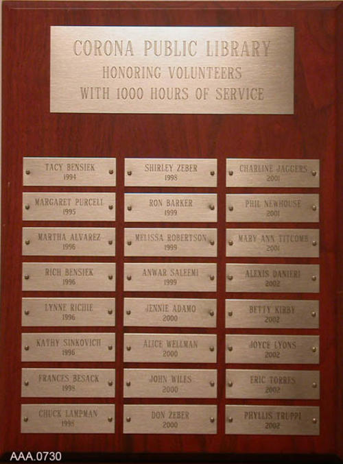 This artifact is a wood plaque honoring Corona Public Library volunteers with 1000 hours of service