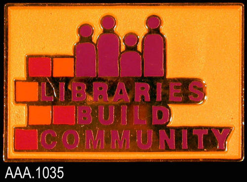 "This artifact is a pin measuring 1 1/2"" x 1"".  The text on the pin reads:  ""Libraries Build Community.""  Above the text is a graphic depicting people."