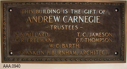 "This artifact is a Ceremonial Artifact.  It is a  brass plaque with the following inscription:  ""This Building is the Gift of - Andrew Carnegie - Trustees - S. S. Willard - T. C. Jamison - G. R. Greeman - W. C. Barth. --Franklin P. Burnham, Architect."""