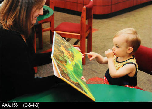 "This artifact is a color photo mounted on foamcore with a lady showing a book to an infant.  This was was used in the promotion of reading.  MEASUREMENTS:  12 5/8"" X 18 3/4"" X 3/16"", CONDITION:  Excellent, COPIES:  1"