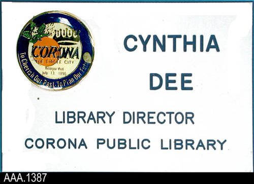 "This artifact is the name badge for Cynthia Dee who served as Library Director from 1972 to 1992.  The badge is white with the city logo in the upper left hand corner.  The blue text reads:  ""CYNTHIA DEE - LIBRARY DIRECTOR - CORONA PUBLIC LIBRARY.""  CONDITION:  There is a small 3-4 mm speck on the logo."
