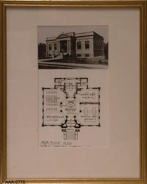 "This artifact is a gold framed, B/W photograph of the old Corona Carnegie Library.  Below the photograph is a small B/W blue print of the main floor plan.  This framed artifact measures 14 1/8"" x 11 1/2""."