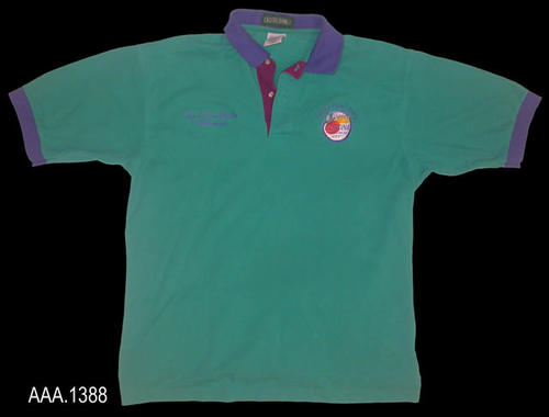 "This artifact is a green T-Shirt with dark blue trim on the sleeves and collar.  The placket has two buttons and is burgandy in color.  On the left side of the shirt is the city logo with the words, ""Corona Public Library,"" arched over the round logo.  On the right in blue script text are the words:  ""Chris Tina Smith - Librarian.""  This T-Shirt is an adult large."