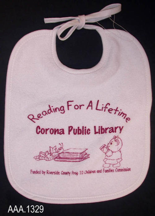 "This artifact is a white, baby's bib.  Imprinted in dark red is the following:  ""Reading For a Lifetime - Corona Publib Library - (two graphics) - Funded by Riverside County Prop 10 Children and Families Commission."":"