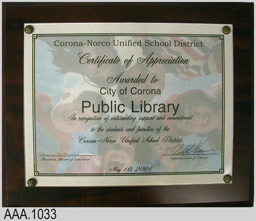 "This artifact is a plaque presented to the Corona Public Library from the Corona-Norco Unified School District.  The text of the plaque reads:  ""Corona-Norco Unified School District  Certificate of Appreciation  Awarded to City of Corona Public Library  In recognition of outstanding support and commitment  to the students and families of the  Corona-Norco Unified School District.   Sharon R. Martinez - President, Board of Education - /s/ Pedro Garcia - Superintendent of Schools.""    CONDITION:  There is some cosmetic damage to the bottom portion of the plaque."