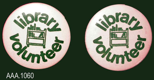 "This artifact collection consist of two idential volunteer buttons with green text on white backgrounds.  The text reads:  ""Library - ( a book cart logo) - Volunteer."""
