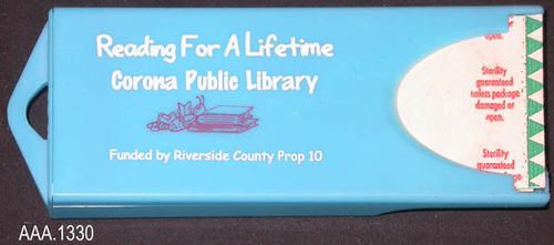 "This artifact is a turquoise, plastic band-aid holder.  Holds about ten standard sized band aids and can be refilled.  The white text on the holder reads:  ""Reading For A Lifetime - Corona Public Library - (a graphic) - Funded by Riverside County Prop 10.""  This artifact measures 3 7/8"" (L), 1 1/2"" (W) and 1/2"" (Thick)."
