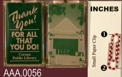 "This artifact is a plastic key ring.  It is green and light-green in color.  On one side is a picture of the entrance to the Corona Public Library.  The opposite side has the following inscription:  ""Thank You! for all that you do!  Corona Public Library.""  QUANTITY:  Two key rings."