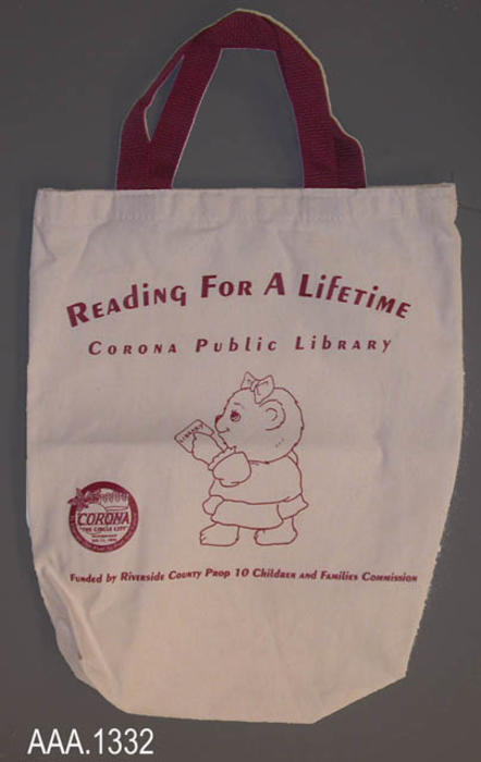 "This artifact is a tan and maroon, canvas, book bag.  On the front of the bag is the following text and logos:  ""Reading For A Lifetime - Corona Public Library - (teddy bear graphic and city logo) - Funded by Riverside County - Prop 10 Commission.""  This bag measures 12 1/2"" x 15 1/4""."