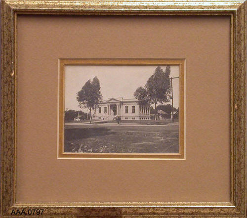 This artifact is a framed photograph of the old Carnegie Public Library in Corona, CA, circa 1920. Donor's Remarks: Maria's sister found the item when she lived at Lemonia Grove on Rimpau Avenue.