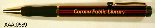 "This artifact is a Red, black, and gold pen.  The words, "" Corona Public Library,"" are written in gold on the top helf of the pen.  CONDITION:  This artifact is in excellent condition."
