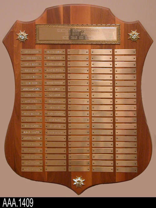 "This artifact is a plaque displaying the names of volunteers who worked 100 hours in the Heritage Room.  The plaque displays thirty-four volunteer names.  CONDITION:  This plaque is in good condition.  MEASUREMENTS:  20"" X 16"".  The plaque is shaped like a shield."
