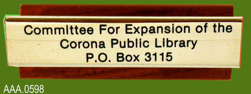 "This artifact is a rubber stamp with text that reads:  ""Committee For Expansion of the Corona Public Library, P. O. Box 3115, Corona, CA 91718-3115."""