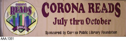 "This artifact is a display banner measuring 119.5"" (L) and 34.25"" (Height).  The banner is beige with plum and black text.  The plum colored text reads:  ""Corona Reads - July thru October.""  The black text reads:  ""Sponsored by Corona Public Library Foundation.""  At the left end of the banner is a 2003 Corona Reads logo."
