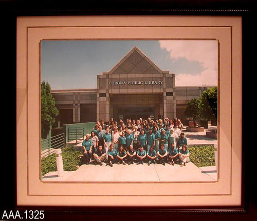 "This artifact is a framed photo of the Corona Public Library Staff taken in September 2000.  It measures 25"" x 29""."