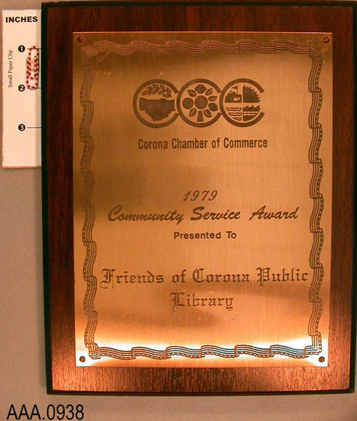 "This artifact is a ceremonial plaque.  It is inscribed as follows:  "" Corona Chamber of Commerce 1979, Community Service Award, Presented to Friends of the Corona Public Library, Dedication."""