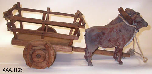"This artifact is a model showing two oxen drawing an old ox cart.  This model measures 20"" x 7 1/2"" assembled in display."