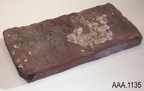 "This artifact is a rectangular, hand made, red clay adobe brick.  Areas of white plaster can be seen on the brick.  This brick measures 12"" x 6"" x 1 1/2"".  CONDITION:  Good Donor's Remarks:  This brick was made during the 1800's.  It was found near the site of the original San Luis Ray Mission."