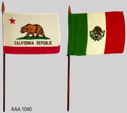 "This artifact collection consists of two flags measuring 5"" x 3"" on wooden staffs.  One flag is the California State Flag; the other flag is the flag of Mexico.  They are designed to be displayed on a small, circular, wooden stand which is missing."