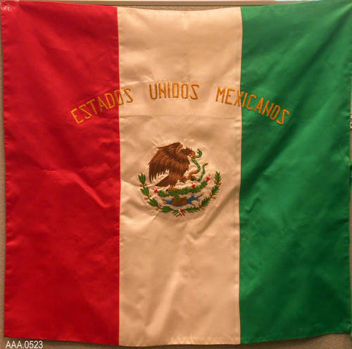 "This artifact is a red, white, and green Mexican flag with the following text:  ""Estados Unidos Mexicanos.""  The country emblem is also present on the flag."