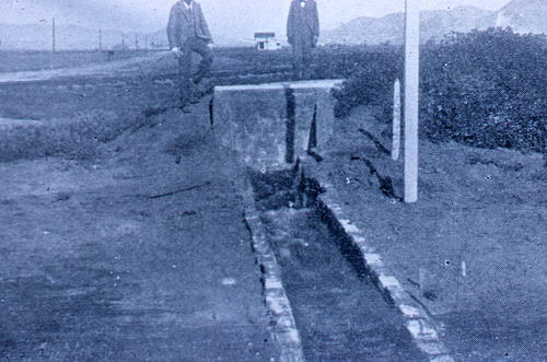 This slide shows early grove irrigation.  Two men in background; however, in the photo the faces do not show.  SLIDE CONDITION:  Color deterioration.  The has a blue cast.