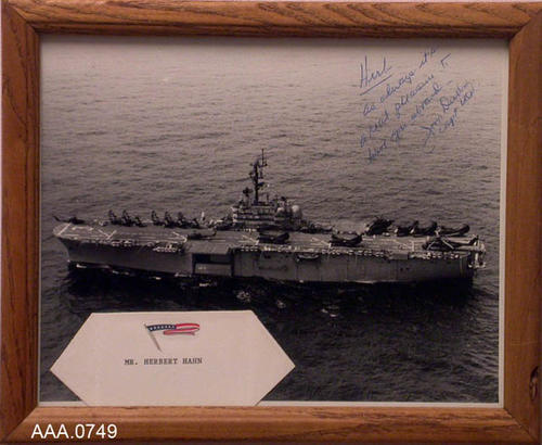 "This artifact is a framed Black and White picture of the USS Okinawa underway.  It has the following signed inscription:  ""Herb - As always it's a real pleasure to have you aboard. Jim Burbid, Capt. USN."""
