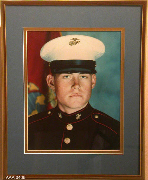 "This artifact is a framed, color photograph of Adam Hoage in his Marine Uniform.  The frame is gold and the photo is matted with a blue and gold matt board.  Adam Hoage was a casualty of the Persian Gulf War, Operation Desert Strom, on February 23, 1991.  This photograph measures 14 1/2""x 11 1/4""."