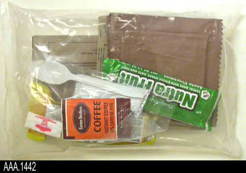 This artifact is a food ration package with a spoon and matches. The items are in a clear, sealed, plastic bag.  Some of the visible items are:  Coffee, spoon, matces, natural fruit bar (2), grape jelly, MRE pouch with heater, salt, crackers,and chili with beans This food ration package is part of the Chris Harvey Eagle Scout Project:  Heroes Of Our Community - Corona, California - 2007.   CONDITION:  Very good.