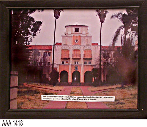 This artifact is a framed picture of the Norconian Hotel located in Norco, CA.  When used as a hospital it served as a facility for those injured at Pearl Harbor and continued to serve as a hospital facility for injured soldiers of WWII. This picture is part of the Chris Harvey Eagle Scout Project:  Heroes Of Our Community - Corona, California - 2007.   CONDITION:  Basically in very good condition; however a reddish area is noted on the right hand side in the tree.