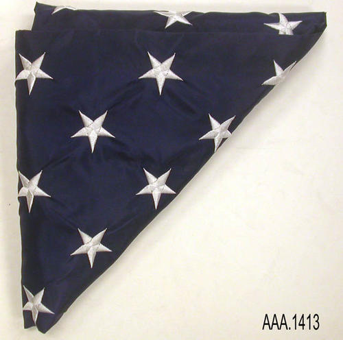This artifact is a folded American flag, and is part of the Chris Harvey Eagle Scout Project:  Heroes Of Our Community - Corona, California - 2007.  When unfolded, this  NYL-GLO, color fast flag.  CONDITION:  Like new.