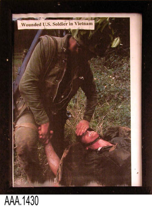 "This artifact is a framed color picture.  The picture shows a wounded U. S. Soldier in Vietnam on the ground with another soldier giving aid..  This framed picture is part of the Chris Harvey Eagle Scout Project:  Heroes Of Our Community - Corona, California - 2007.     MEASUREMENTS:  12"" x 9 1/2"". CONDITION:  The framed picture is in good condition."