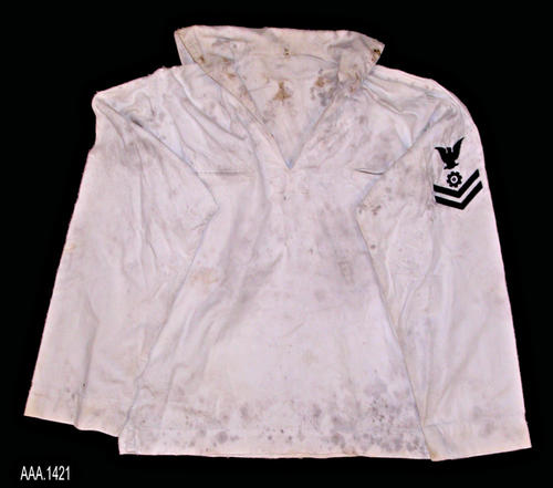 This artifact is a white, Navy, sailor's shirt.   This shirt is part of the Chris Harvey Eagle Scout Project:  Heroes Of Our Community - Corona, California - 2007.   CONDITION:  The shirt shows extensive mold damage.   On the back of the shirt there are several large holes.