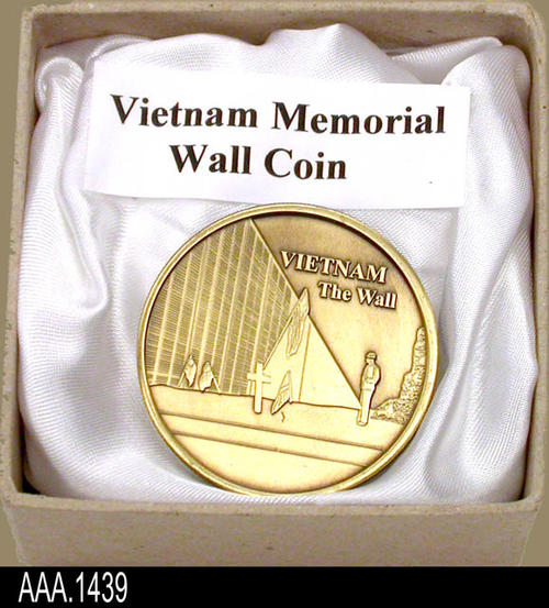 "This artifact is a Vietnam Memorial Wall Coin.  The face of the coin depicts the Memorial Wall with a person viewing it. The coin is in a 2 3/4"" inch square, light tan cardboard box. This Vietnam Memorial Wall Coin is part of the Chris Harvey Eagle Scout Project:  Heroes Of Our Community - Corona, California - 2007.   MEASUREMENTS:  Coin diameter is 1 1/2"".   - CONDITION:  Excellent."