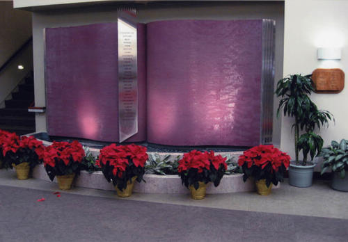 Photograph of the Library's Water Wall which was in the lobby on the south wall. In front of the fountain are a series of poinsettias. The Friends decorate the Library with wreaths and poinsettias every December to add some festive color to the season.