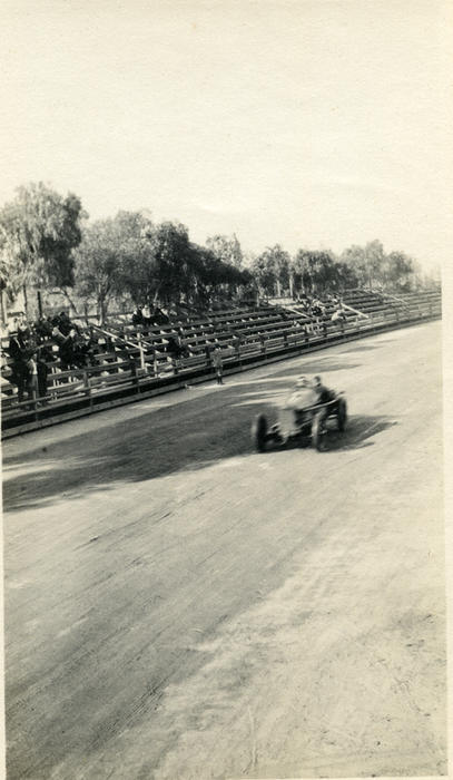 Race car on the street with spectators watching from the grandstands, New
