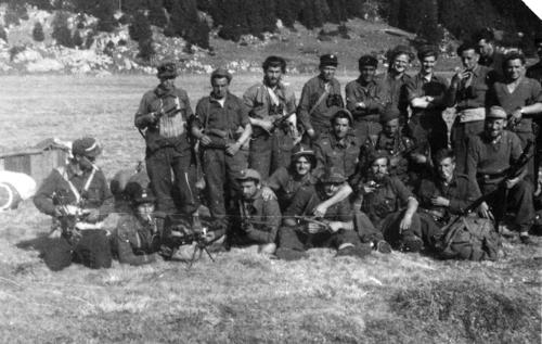 The first half of a panoramic photograph taken during World War II. Phil Newhouse was taken in by the Italian Partisans after his B-25 was downed over northern Italy. He worked with the Partisans to create an airstrip and airdrop location used by the British military during the war. The photograph was taken by an English RAF Captain who tracked down Mr. Newhouse after the war and mailed him copies of the photos he'd taken of the group. The Partisans in the photo are unidentified; Phil Newhouse is in the back row, sixth from the left., This is a digital image, the original was returned to the donor after scanning.