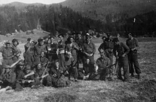 Phil Newhouse and Italian Partisans preparing for a group photograph. Phil Newhouse was taken in by the Italian Partisans after his B-25 was downed over northern Italy. He worked with the Partisans to create an airstrip and airdrop location used by the British military during the war. The photograph was taken by an English RAF Captain who tracked down Mr. Newhouse after the war and mailed him copies of the photos he'd taken of the group. The Partisans in the photo are unidentified; Phil Newhouse is in the back row, fifth from the left., This is a digital image, the original was returned to the donor after scanning.