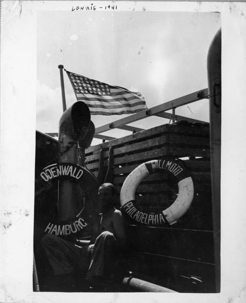 Photograph of a Abner Lonnie Alton on the captured German ship, <em>Odenwald</em>. The two life preservers show the original name that the ship was using, <em>Willmoto</em> out of Philadelphia, and the ship's correct name, <em>Odenwald</em> out of Hamburg. The <em>USS Omaha</em> captured the <em>Odenwald</em> in the Atlantic. Abner Lonnie Alton served on the <em>USS Omaha</em> before and during World War II., This is a digital image, the original was returned to the donor after scanning.
