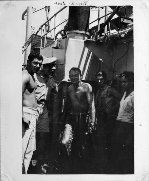 Photograph of the <em>USS Omaha</em> crew members possibly repairing the captured German ship, <em>Odenwald</em>. The crew of the <em>Odenwald</em> attempted to scuttle the ship, but the Omaha crew prevented the sinking of the vessel. Abner Lonnie Alton served on the <em>USS Omaha</em> before and during World War II, he is in the center of the photograph smiling at the camera., This is a digital image, the original was returned to the donor after scanning.