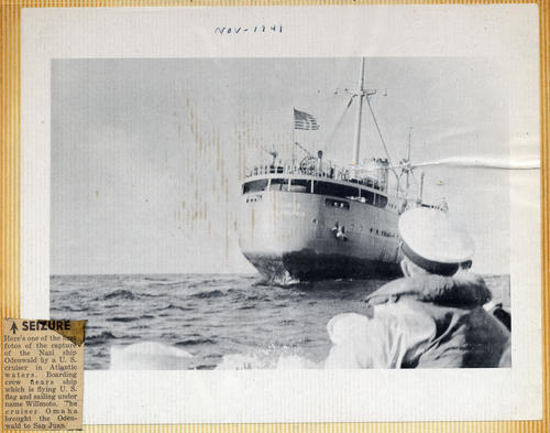 Photograph of the <em>Odenwald</em>, a Nazi ship disguised as an American ship, <em>Willmoto</em>. A newspaper clipping is attached to the lower left corner of the image, it discusses the capture of the Nazi ship by the U.S. Navy's <em>USS Omaha</em>. Abner Lonnie Alton served on the Omaha before and during World War II., This is a digital image, the original was returned to the donor after scanning. The vertical lines are due to the adhesive used to adhere the photo to the photo album page.