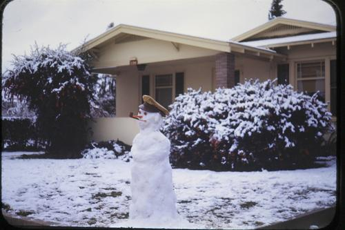 "This photo was taken in the front yard of 724 West 11th Street in January, 1949 when Southern California experienced snowfall from January 9th through January 12th. This photo is courtesy of Robert ""Ed"" Munn, who as a young boy of 14, took photos of Corona in the late 1940's. Photography was one of his hobbies. Ed Munn was the son of Dr. & Mrs. William B. Munn DDS and his family lived on West 11th St in Corona from 1938 to 1959., The description is from the donor's note on the back of the photograph."
