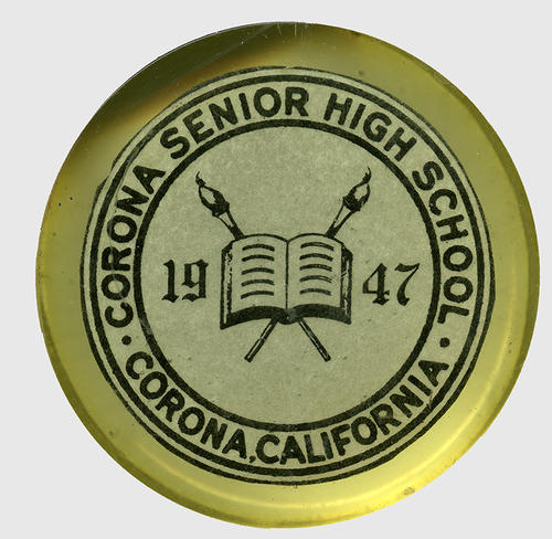 "Paperweight, ""Corona Senior High School - Corona, California"" on the outer edge of the circular emblem. The center ""1947"" with an open book and two torches behind the book. Lettering is in blue."