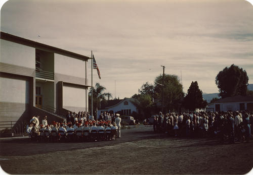 Dedication Ceremony for Corona Junior High School. The ceremony took place on the lawn behind the newly constructed school. The Corona Junior High School Band is on the left, while the attendees are standing for the Pledge of Allegiance.