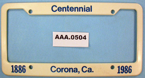 "Vehicle license plate holder with the phrase, ""Centennial - 1886 - Corona - 1986"" written on it."