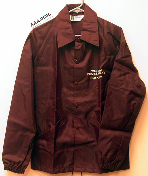 "Dark maroon windbreaker, size small, with the words ""Corona Centennial 1886-1986"" written on it as well as the City Seal."