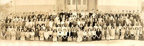 Panoramic photograph of the Class of 1948. The class is lined up in front the rear entrance to the new Corona Junior High School on Main Street.