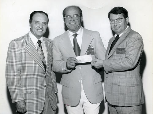 Photograph taken for the Corona Daily Independent. Al Stewart, in the center, Exalted Ruler, Corona Elks, presenting a check to L. James Nekitas, President of California-Hawaii Elks, and Yubi Separovich. Photo was published in the Corona Daily Independent newspaper on Monday, June 10, 1974 on page 6. More information about the fundraising done by the Elks accompanies the published photo.