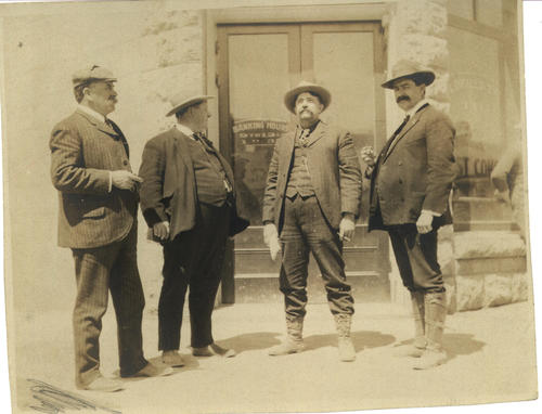 Four Men in suits, hat and boots standing  outside the bank. Two  are identified as Mr. Baird and Mr. Stobbs-Tin Miners; the other men are unknown but are miners as well.