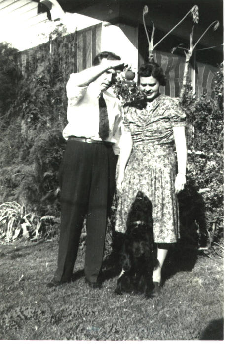 Man and woman playing with dog, possibly the McNeils.